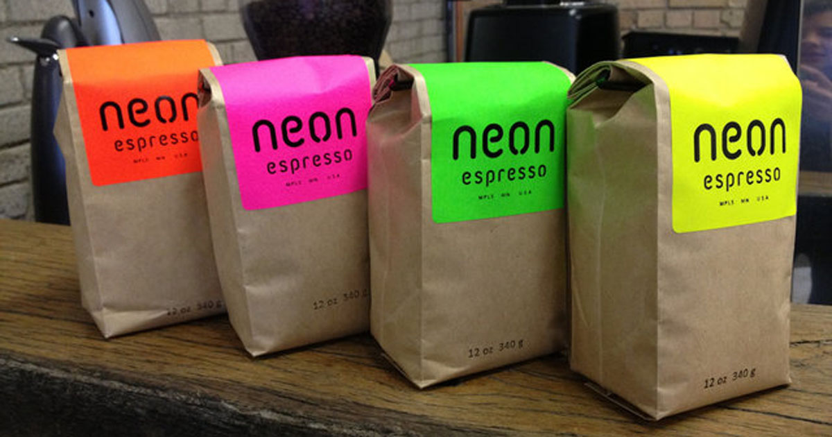 Brown paper coffee bags sealed with neon product labels in various colours to distinguish different flavors/brews