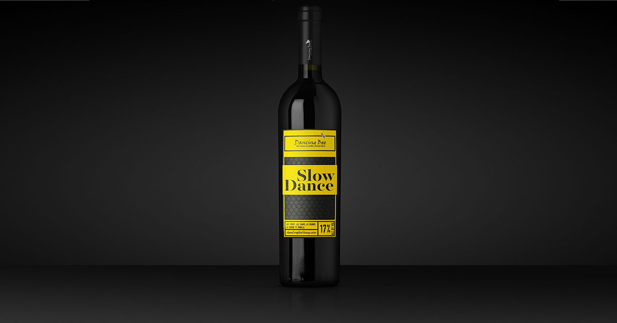 Black glass wine bottle label with a neon yellow product label